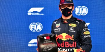 Max Verstappen holding his signed Pirelli Pole Position Award tyre