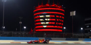 Carlos Sainz drives past the Bahrain tower displaying the Ferrari logo during Friday's FP2 session