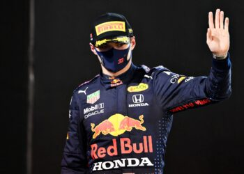 Max Verstappen waves as he walks onto the podium