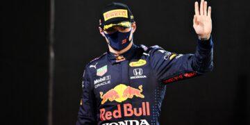 Max Verstappen waves as he walks onto the podium