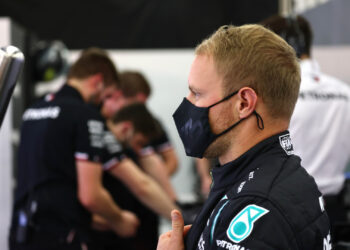 Profile of Bottas standing in the garage with team members working in the background